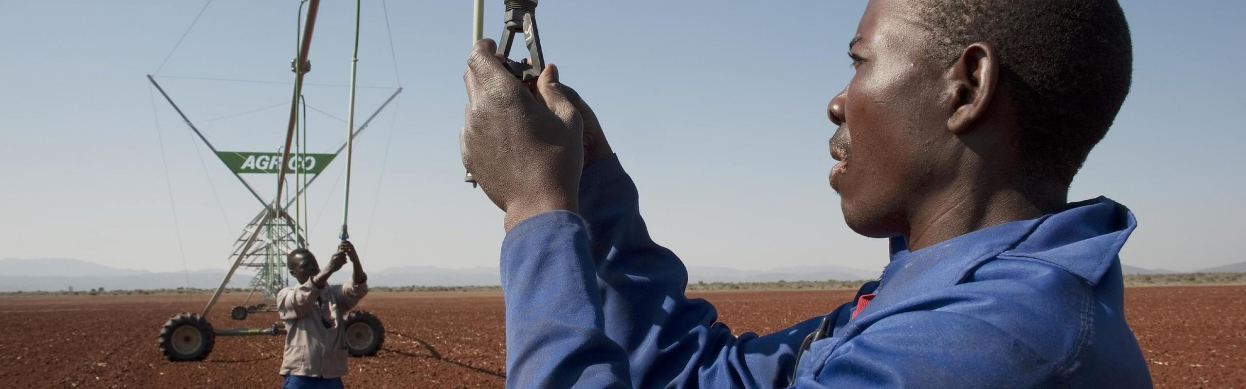 Two men prepare irrigation equipment on a field  in Strydkraal, South Africa